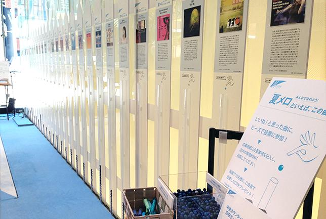 来訪者参加型の展示。パネルに付属する筒にブルーの玉を入れて投票する。